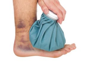 young male icing a sprained ankle with ice pack (isolated on white background)